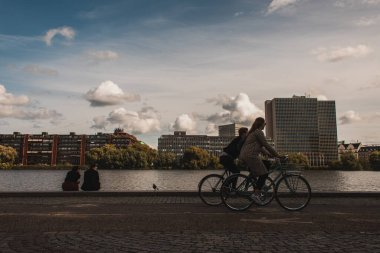 COPENHAGEN, DENMARK - APRIL 30, 2020: People riding bicycles on promenade near canal with buildings and cloudy sky at background stock vector