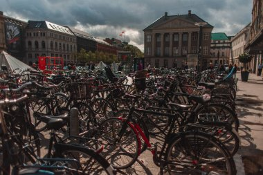 COPENHAGEN, DENMARK - APRIL 30, 2020: Selective focus of bicycles on urban street with buildings and cloudy sky at background stock vector
