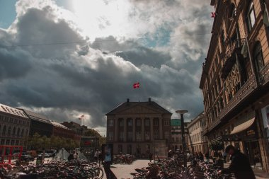 COPENHAGEN, DENMARK - APRIL 30, 2020: Bicycles on city square with buildings and cloudy sky at background