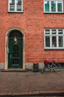 Bicycle near brick facade of building on urban street in Copenhagen, Denmark stock vector