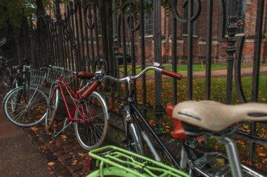 Selective focus of bicycles near fencing on urban street in Copenhagen, Denmark stock vector