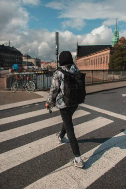 Back view of man walking on crossroad on sunlit street in Copenhagen, Denmark
