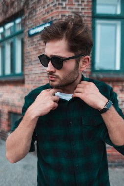 Young man in sunglasses adjusting shirt on urban street, Copenhagen, Denmark stock vector