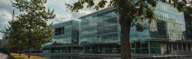 Panoramic shot of trees and glass facade of building near canal, Copenhagen, Denmark stock vector