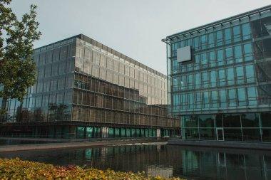 Glass facades of buildings near canal and blue sky at background, Copenhagen, Denmark stock vector
