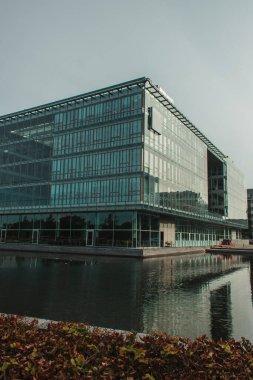 Selective focus of building with glass facade near canal on urban street in Copenhagen, Denmark stock vector