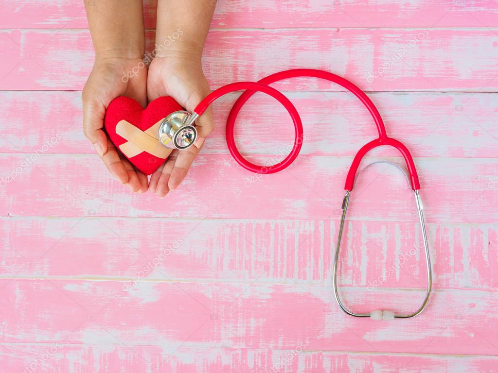 Health and medical, love and valentine concept. Red heart on a woman hand with red stethoscope on the pink wood background