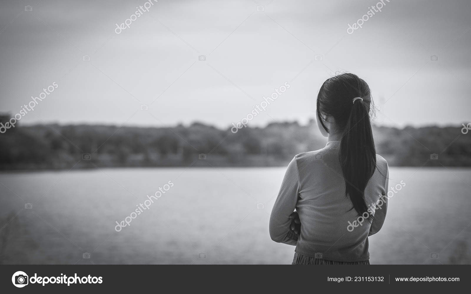 Black and white lonely woman standing alone beside the river lonely sadness concept stock image