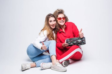Two young women holding wireless speaker and listening music