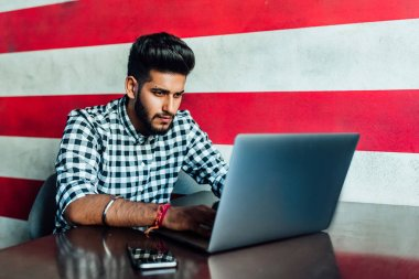 Attractive man in casual clothes using laptop, selective focus