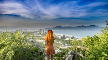 Travel girl with red hair is travelling in Marble Mountains ,staying on the top and watching a view of the Da Nang city on sunset with junles,sea and mountains in Vietnam, travel concept