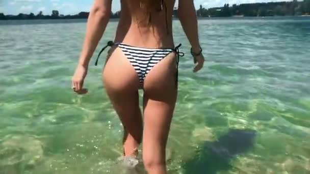 girl with beautiful round buttocks walks in the sea