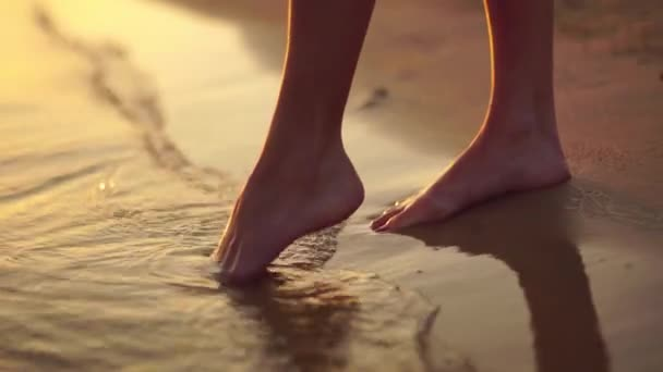 close up of female feet at sunset in the sea