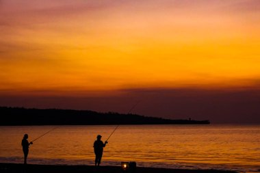 Fishermen on the beach on the island of Bali at sunset.