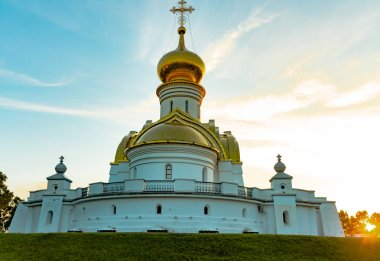 Beautiful view during sunset at the temple of St. Seraphim of Sarov in the city of Khabarovsk. A beautiful green lawn in the foreground. Religious architecture, buildings and traditions. Russia.