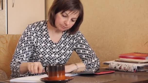 Egy nő kézírásos szöveg egy golyóstollal írja a notebook.