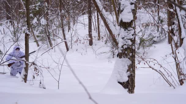 A hunter in white winter camouflage with two barrels shotgun goes in winter forest.