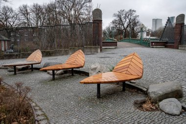 Autumn landscape with empty wooden deck chairs on grey stone pavement background in Berlin Germany. Unusual wood benches. Grunge textures. Fall backdrop in shades of brown and grey.