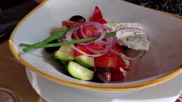 Ruce držící řezání vidličkou a nožem a odebírající ingredience z talíře domácího zeleninového salátu se sýrem Feta a zelenou cibulí. Regionální jídlo Řecka. Zdravé jídlo detailní