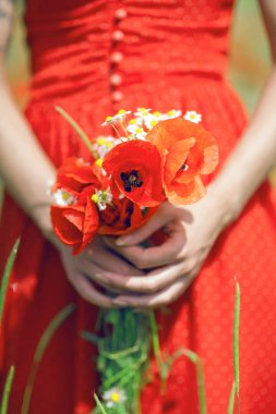beautiful woman in red dress standing in a poppy field holding flowers, close up on her hands with poppies, can be used as background