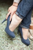 Fotografie young womans feet close up in a street cafe, urban mood, blue jeans and high heels