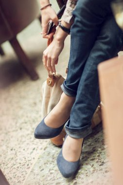 young womans feet close up in a street cafe, urban mood, blue jeans and high heels