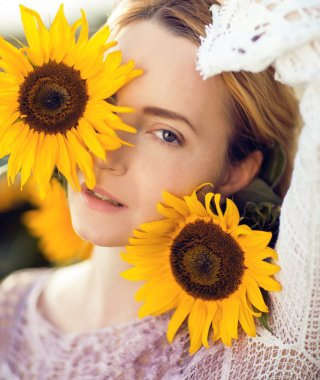Beautiful blonde woman portrait close up, with sunflowers in a rural field outdoors, lust for life, summerly, autumn mood