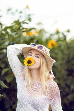 Beautiful woman in a rural field scene outdoors, with sunflower and sunhat, lust for life, summerly, autumn mood
