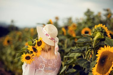 Beautiful blonde woman with long hair and sunhat in a rural sunflowers field outdoors, view from behind, lust for life, summerly, autumn mood