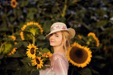 Beautiful woman in a rural field scene outdoors, with sunflowers and sunhat, lust for life, summerly, autumn mood