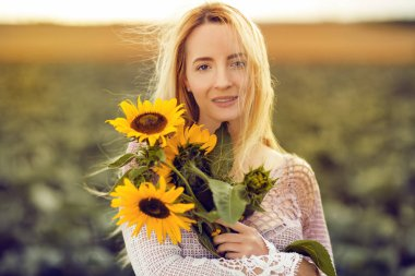 Beautiful woman in a rural field scene outdoors, with sunflowers, lust for life, summerly, autumn mood