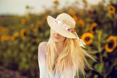 Beautiful blonde woman with long hair and sunhat in a rural sunflowers field outdoors, lust for life, summerly, autumn mood
