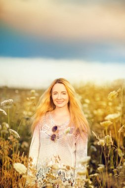 Beautiful blonde woman with long hair standing in a rural flower field outdoors, lust for life, summerly, autumn mood