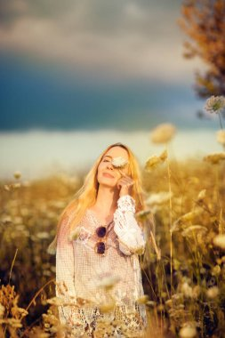 Beautiful woman in a flower meadow with sunglasses and flower, lust for life, summerly, autumn mood