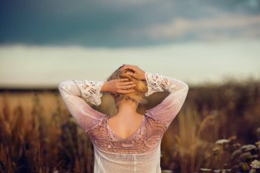 Beautiful blonde woman with long hair standing in a rural flower field outdoors, raising her hair, lust for life, summerly, autumn mood, view from her back