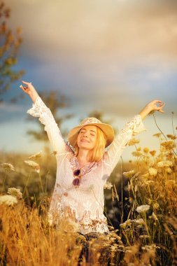 Beautiful woman in a flower meadow with sunhat and sunglasses, lust for life, summerly, autumn mood