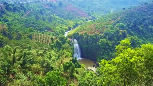 drone approaches amazing high foamy waterfall among tropical wild rainforest on mountain hills