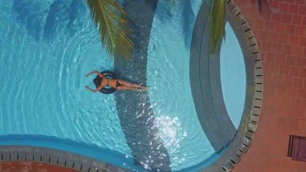 pohled shora holka s pěknou postavou leží v žaludku na kruhu v obrazové fondu a plave, pouze nohama