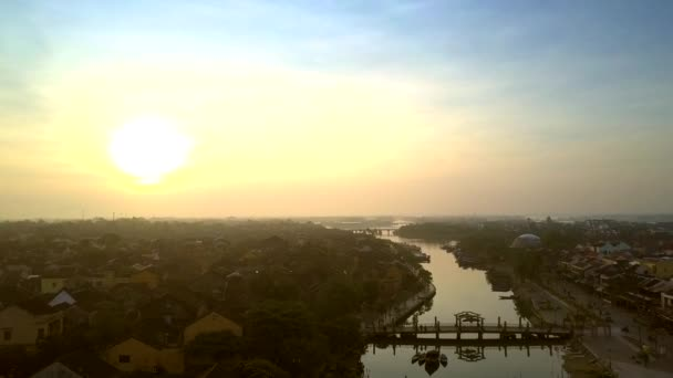 amazing picture boundless orange sky with sun disk above ancient Hoi An dark town with wide river