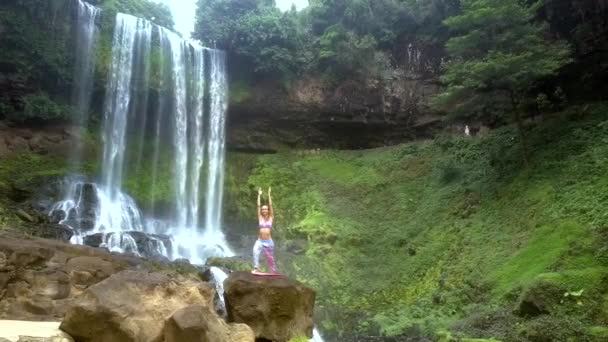wonderful view girl holds yoga pose with hands up on stone against water falling from height in national park