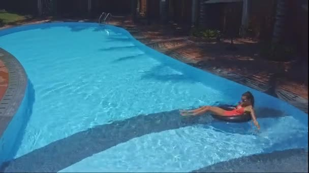 blonďatá dívka plave na nafukovací prstenec v bazénu