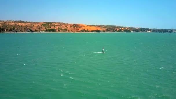 windsurfer szörfözés türkizkék óceán hullám címerek és habos nyoma ellen barna parti vonal feletti repülés