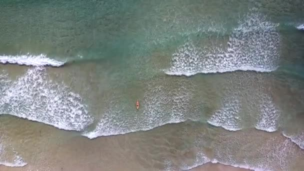 flycam descends to woman surfing on board in shallow transparent foamy ocean waves under sun rays