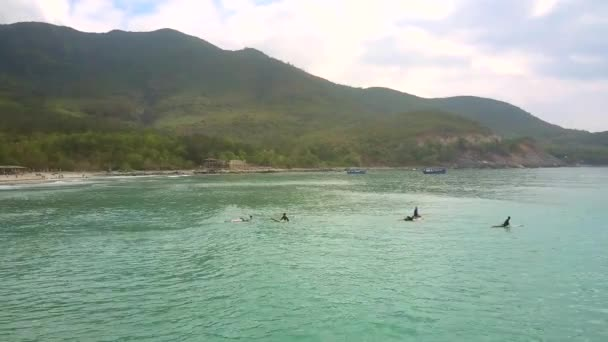 aerial panorama distant surfer beginners try to swim on surfboards against dark hilly coast