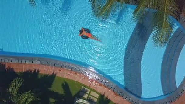 Schlanke Frau verbringt Wochenende mit Schwimmen auf Rettungsring im Pool bei Sonnenschein