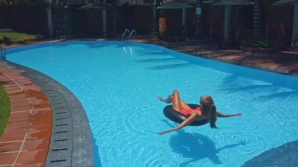 dívka v oranžové bikiny leží na nafukovací prstenec opalování v bazén s průzračnou vodou