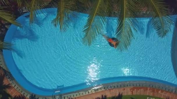 tropischer Wind weht mit großen Palmenblättern über einem erstaunlichen Swimmingpool, in dem ein Mädchen im Ring liegt