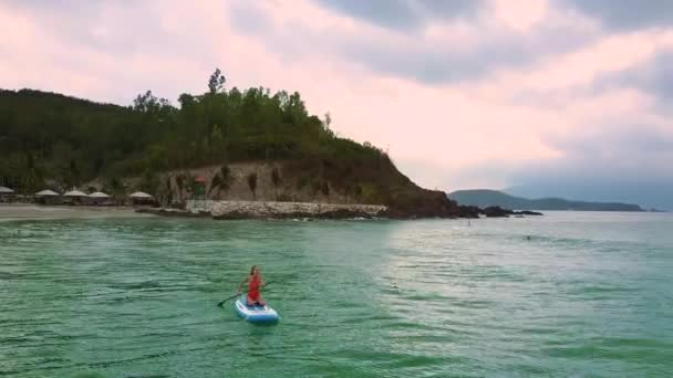 exotic upper view slim girl in red bikini swims sitting on paddleboard turning from sand beach with tents to open azure ocean