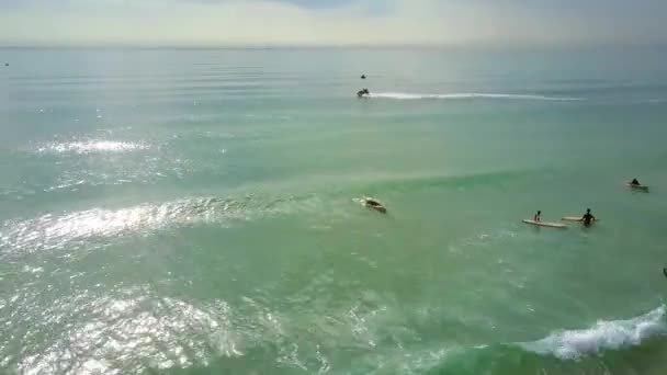surfers sail on boards by beach scooter drives to ocean