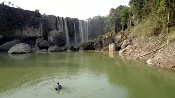flycam shows boy fishing in river against waterfall